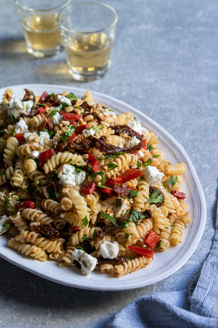 Pasta Salad with Sundried Tomatoes, Roasted Red Pepper, Feta and Tangy Goat's Yoghurt Dressing www.thefoodiecorner.gr Photo description: A close view of a platter with tossed pasta salad. In the background two small glasses of white wine.