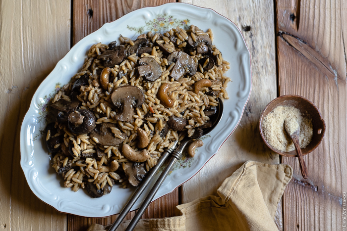 Plant-Based Slow Cooker Balsamic Mushroom Orzotto with Cashews and Sage www.thefoodiecorner.gr photo description: A large platter of balsamic mushroom orzotto, two serving spoons placed to the side of the food. To the bottom right of the image is a bunched up linen napkin and a small wooden bowl with nutritional yeast flakes.