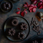 Chocolate and Beetroot Mini Bundt Cakes with a Quick Ganache (Plant Based) www.thefoodiecorner.gr Photo description: Overhead view of mini bundt cakes on a dark plate. Around the plate are some pretty autumn leaves, some chopped chocolate and some cocoa powder. In the two corners of the photo are some more bundt cakes.