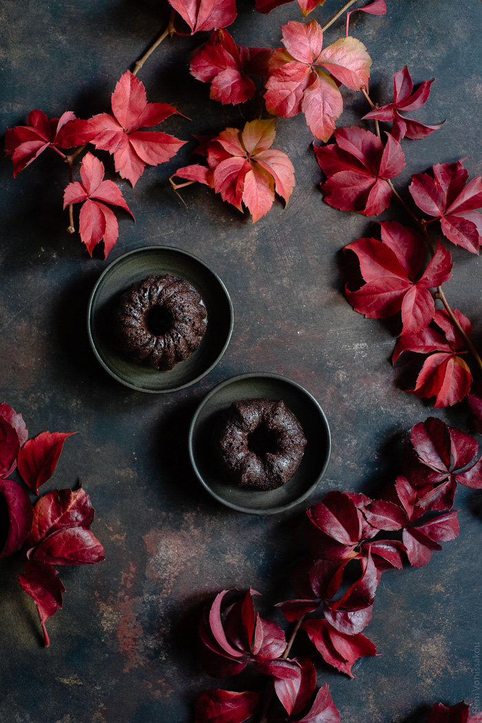 Chocolate and Beetroot Mini Bundt Cakes with a Quick Ganache (Plant Based) www.thefoodiecorner.gr Photo description: Two small plates each with a mini budnt cake on top. Surrounding the plates are lots of pretty autumn leaves.