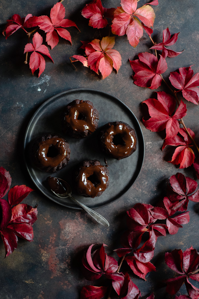Chocolate and Beetroot Mini Bundt Cakes with a Quick Ganache (Plant Based) www.thefoodiecorner.gr Photo description: A plate of mini bundt cakes with a ganache topping. Surrounding the plate are lots of pretty autumn leaves.