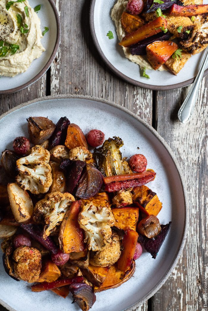 "Cumin Roasted Root Vegetable Medley. My Winter ""Briam"". www.thefoodiecorner.gr Photo description: A closer view of the roasted root vegetables (winter briam) on a ceramic dish. To the top right, half visible, is a small plate with hummus and roasted veg."