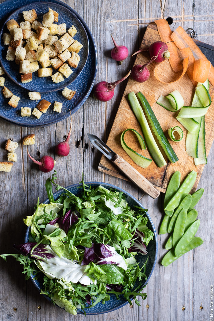 Green Salad with Cucumber, Radishes, Homemade Croutons and Grape Must Vinaigrette www.thefoodiecorner.gr Photo description: A bowl of salad leaves next to a chopping board with a peeler and slices of cucumber and carrot on it. To the top of the photo is a small plate with croutons.