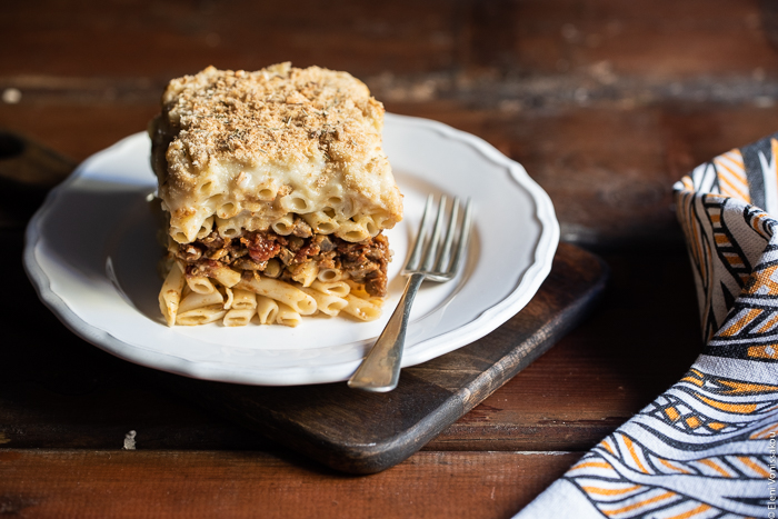 Pastitsio (Greek Pasta Bake) with Lentil and Mushroom Sauce, and Oat Milk Bechamel www.thefoodiecorner.gr Photo description: A slice of pastitsio on a pretty plate sitting on a chopping board. A fork lies next to the slice on the plate.