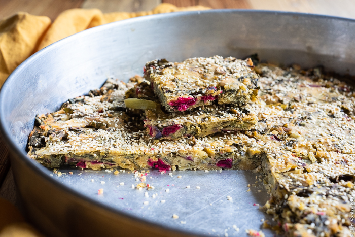 "Easy Greek ""Flour Pie"" with Cornmeal, Spelt and Mixed Greens (Spinach and Beets) www.thefoodiecorner.gr Photo description: A close side view of the pie with some slices removed and placed one on top of the other so as to reveal the pink beetroot stems inside."