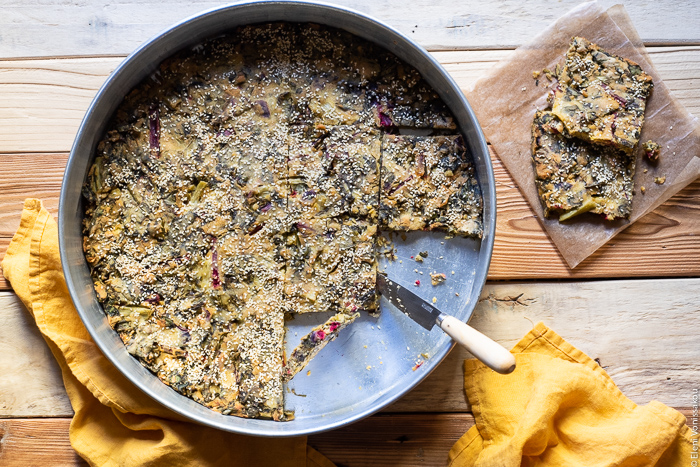 "Easy Greek ""Flour Pie"" with Cornmeal, Spelt and Mixed Greens (Spinach and Beets) www.thefoodiecorner.gr Photo description: A large baking tin containing a cooked greens pie. Some slices have been removed and placed on a piece of baking paper at the side of the tin. A knife is lying over the edge of the tin, its tip touching the pie. To the bottom of the tin are two linen napkins."