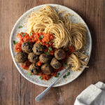 "Aubergine (Eggplant) ""Meatballs"" with Tomato Sauce and Spaghetti www.thefoodiecorner.gr Photo description: A large ceramic plate full of spaghetti with sauce and aubergine meatballs on top. The plate is on a wooden surface. To the bottom is a bunched up linen napkin."