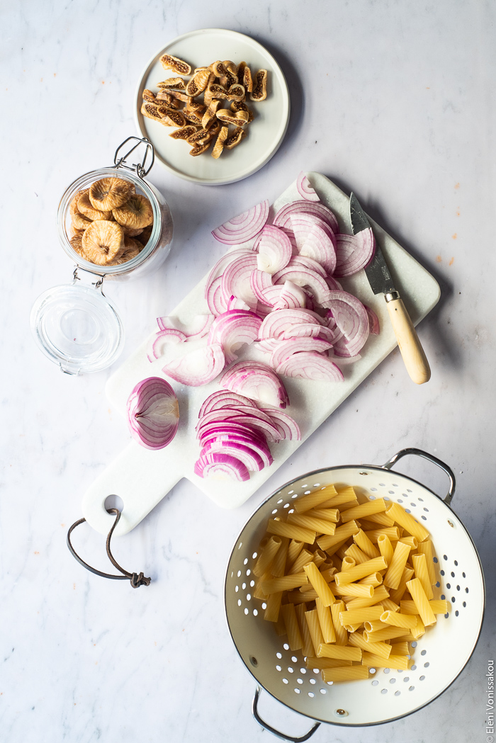 Caramelised Onion, Fig and Fresh Cheese Pasta with Arugula www.thefoodiecorner.gr Photo description: A small plate of chopped figs, a jar of whole dried figs, a chopping board with sliced onions and a knife on it, and a colander with dried rigatoni pasta inside.