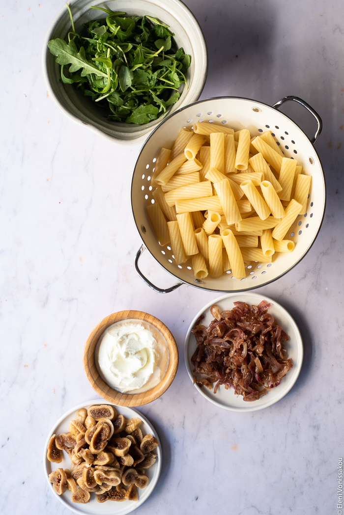 Caramelised Onion, Fig and Fresh Cheese Pasta with Arugula www.thefoodiecorner.gr Photo description: A bowl of arugula, a colander with boiled rigatoni pasta inside, a small plate of caramelised onions, a bowl of fresh cheese and a small plate of reconstituted figs.
