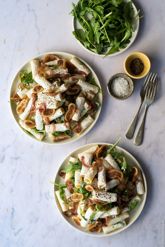 Caramelised Onion, Fig and Fresh Cheese Pasta with Arugula www.thefoodiecorner.gr Photo description: two plates of pasta on a marble surface. To the top right are two small bowls of salt and pepper, two forks and a small plate of extra arugula.