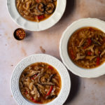 Slow Cooker Hot and Sour Cabbage Soup with Shiitake Mushrooms www.thefoodiecorner.gr Photo description: Three bowls of soup on a marble surface. At the side of one is a tiny bowl with chilli flakes.