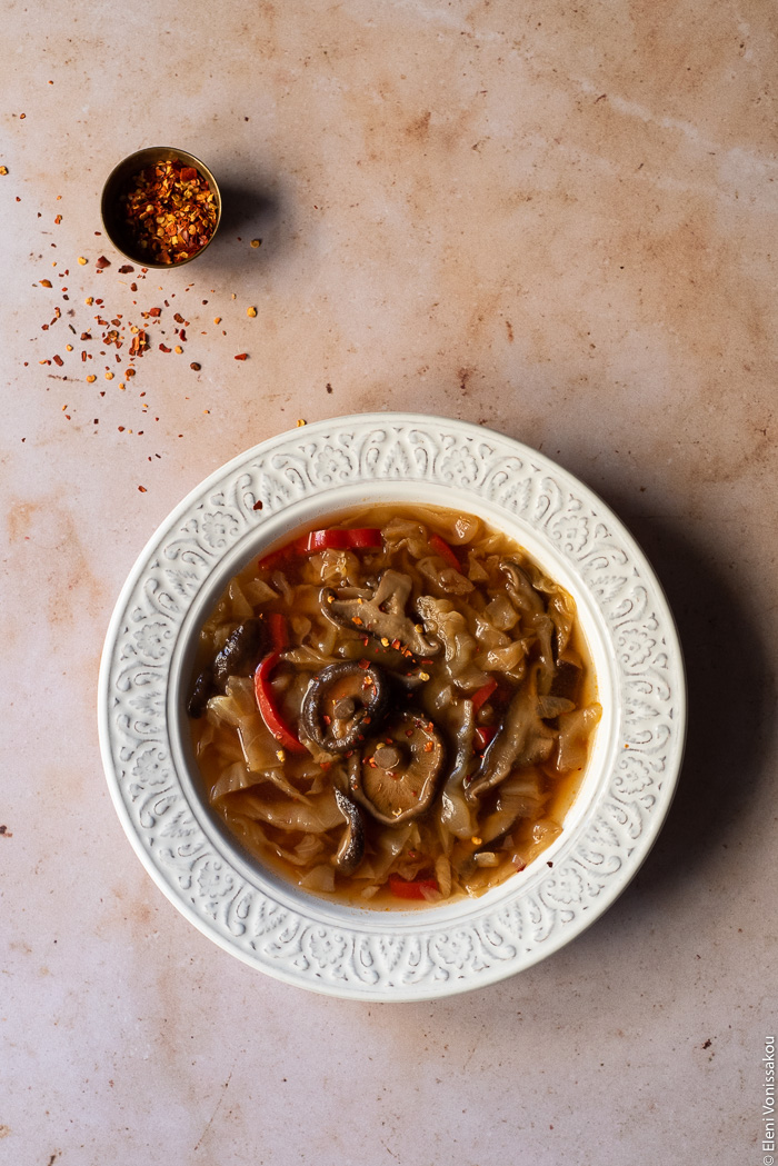 Slow Cooker Hot and Sour Cabbage Soup with Shiitake Mushrooms www.thefoodiecorner.gr Photo description: One bowl of soup on a marble surface. A bit further away is a tiny bowl of chilli flakes, with some of the flakes scattered on the marble.