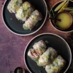 Shiitake, Rice and Truffle Oil Stuffed Cabbage Rolls with Lemon Vinaigrette www.thefoodiecorner.gr Photo description: Two plates with stuffed cabbage rolls on a rusty coloured surface. One of the rolls is cut showing the rice stuffing inside. In the top right corner of the image is a small plate with slices of lemon and a small bowl of vinaigrette.