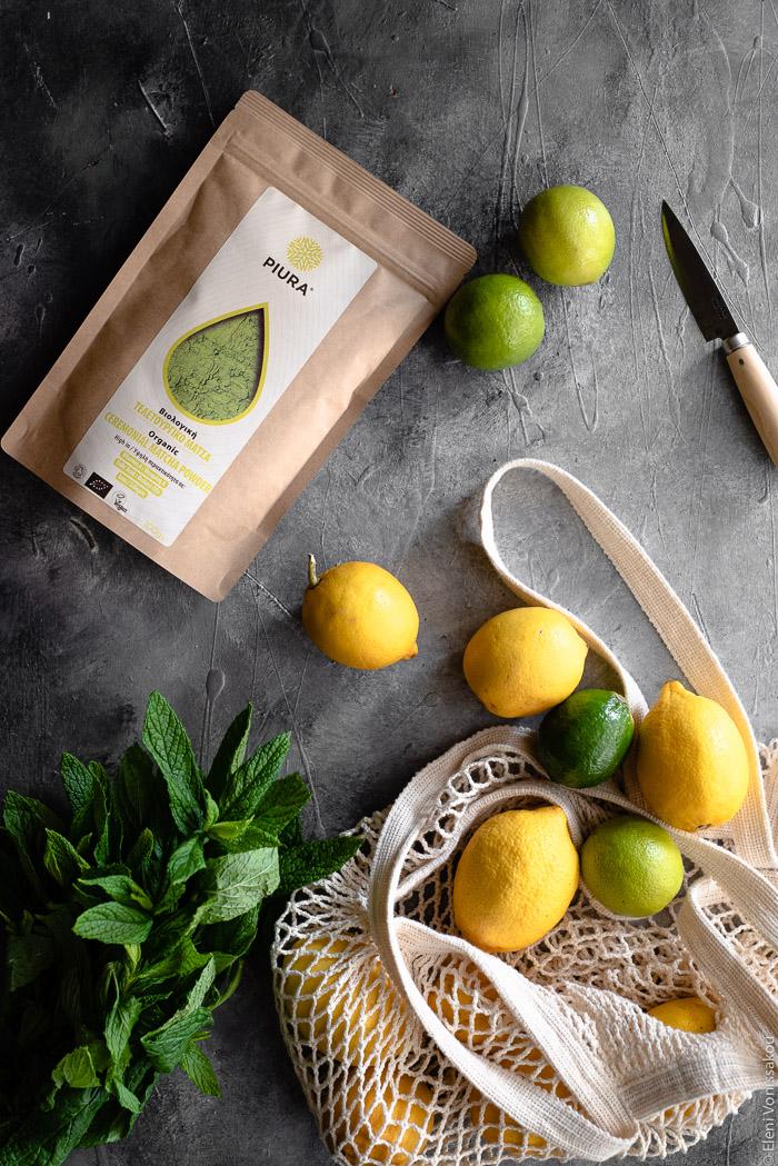 Σπιτική Λεμονάδα με Τσάι Matcha www.thefoodiecorner.gr Photo description: A string bag with lemons and limes spilling out. To the side of it a bunch of spearmint. To the top of the photo is a packet of Piura matcha and a sharp knife.