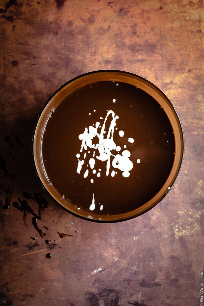 Μους Αλατισμένης Σοκολάτας με Ελαιόλαδο www.thefoodiecorner.gr Photo description: Top down view of a large glass bowl of mousse mixture (looks like melted milk chocolate) with some blobs of white coconut milk on the surface.