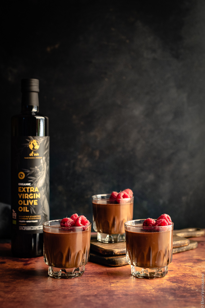 Easy, Egg-Free Olive Oil Chocolate Mousse www.thefoodiecorner.gr Photo description: Side view of three glasses of chocolate mousse against a dark background. The mousse is garnished with raspberries. The glass furthest away is sitting on two wooden chopping boards, thus it is slightly higher than the front two. To the left is a bottle of olive oil.