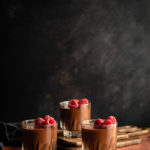 Easy, Egg-Free Olive Oil Chocolate Mousse www.thefoodiecorner.gr Photo description: Side view of three glasses of chocolate mousse against a dark background. The mousse is garnished with raspberries. The glass furthest away is sitting on two wooden chopping boards, thus it is slightly higher than the front two.