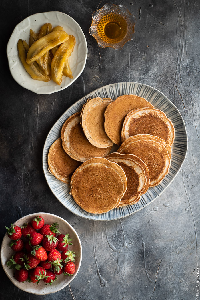 Spelt Pancakes with Honey Fried Bananas (egg and dairy free) www.thefoodiecorner.gr Photo description: A ceramic platter full of pancakes. To the bottom of the platter is a small plate of strawberries and to the top is a plate of fried bananas and a small bowl of honey.