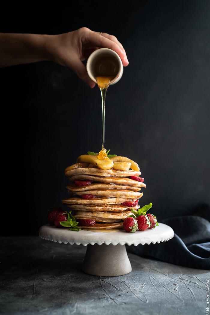 Pancakes με Αλεύρι Σπέλτ και Μελωμένες Τηγανιτές Μπανάνες (χωρίς αυγά) www.thefoodiecorner.gr Photo description: A stack of spelt pancakes on a small ceramic cake stand garnished with honey fried bananas on top and strawberries all around. A hand is pouring honey over the top of the stack and it is dripping down the side of the pancakes.