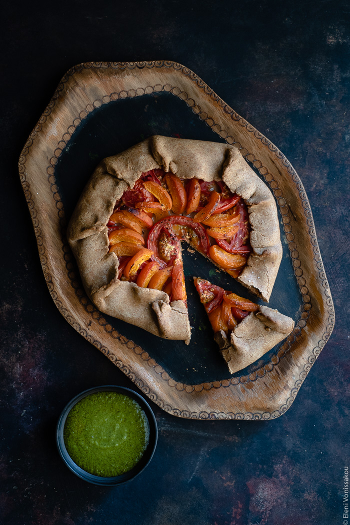 Apricot and Tomato Spelt Galette with Basil Vinaigrette www.thefoodiecorner.gr Photo description: A galette with apricot and tomato slices arranged nicely inside. The galette is on a wooden tray and one slice has been cut and pulled out slightly. At the bottom left of the photo is a small bowl of basil vinaigrette.