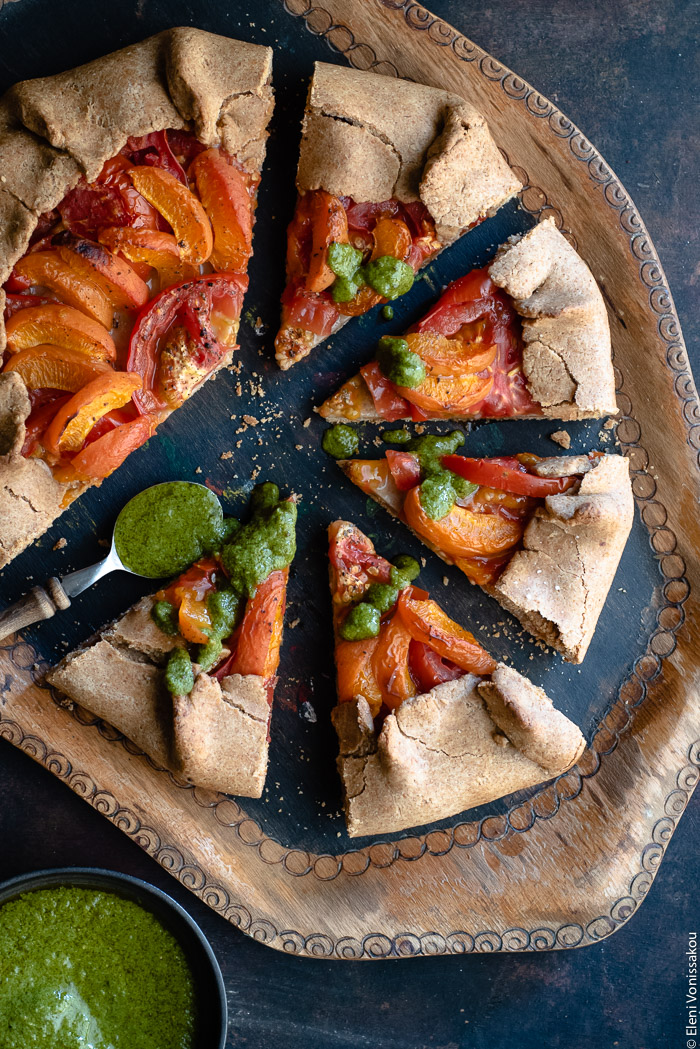 Apricot and Tomato Spelt Galette with Basil Vinaigrette www.thefoodiecorner.gr Photo description: A wooden tray with a galette on it, most of it cut into slices that have been slightly pulled out. Beside one of them is a small spoon with basil vinaigrette, some of which has been drizzled on the slices. In the bottom left corner is a small bowl of vinaigrette, half visible.