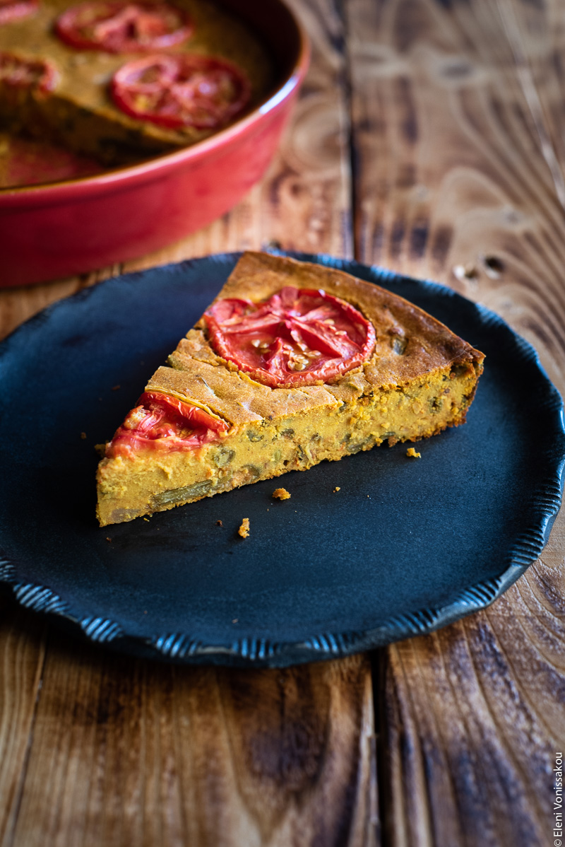 Chickpea Flour Pie (aka Plant-Based Frittata) with Leftover Green Bean Stew www.thefoodiecorner.gr Photo description: A black ceramic plate with a pretty pattern around the edge, and a slice of chickpea flour pie on it. The pie is decorated with slices of tomato on top which have cooked down while baking.