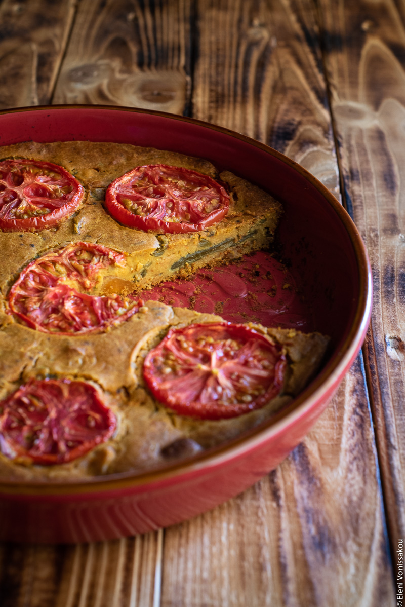 Chickpea Flour Pie (aka Plant-Based Frittata) with Leftover Green Bean Stew www.thefoodiecorner.gr Photo description: a red baking dish with a pretty pattern on the inside. A slice has been removed and there are some green beans barely visible from the side inside the pie.